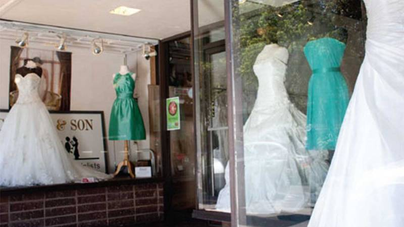 Wedding attire shop windows with wedding dresses displayed.