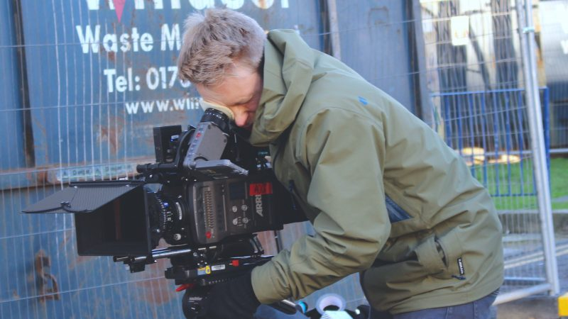 camera operator with a camera on a tripod