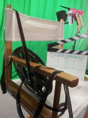 Film spilling out of a film canister on a director's chair with a movie slate.