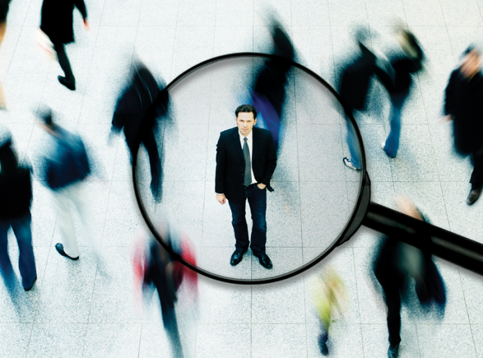 A man under a magnifying glass is in focus while all others around him are blurred.