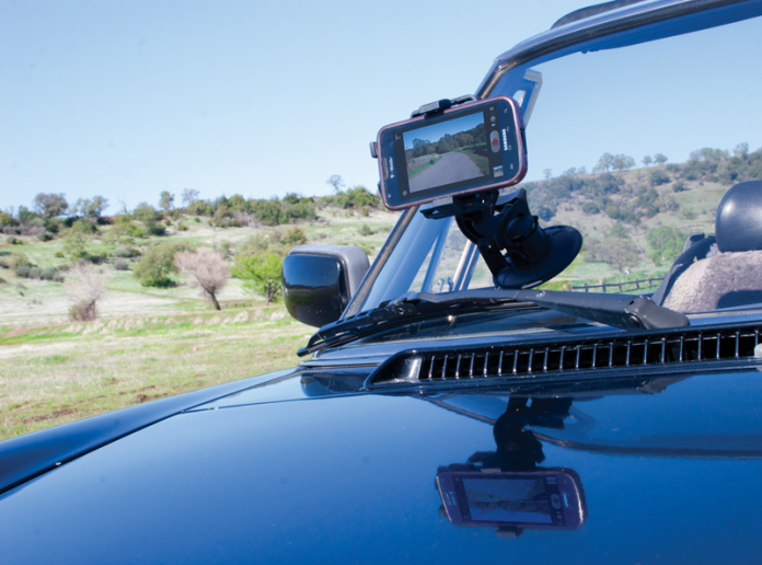 Shot of a smartphone attached to a suction-cup stabilizer on a car