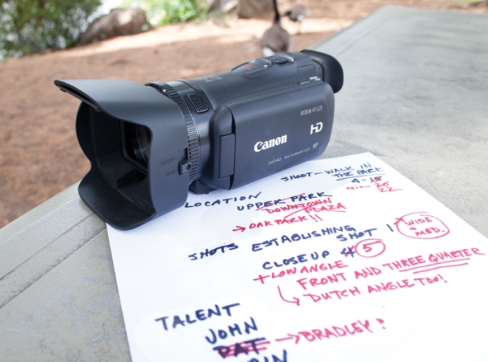 HD camcorder sitting on shot list on table in park.