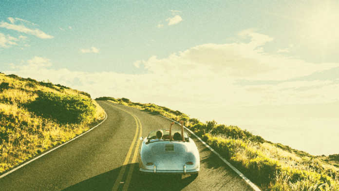 Convertable driving along curved road with retro color grading.