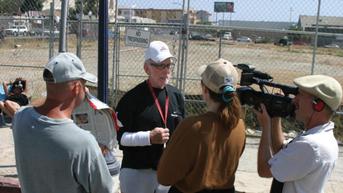 """Producer Patty Mooney and her husband/partner DP Mark Schulze interview Dave """"The Waterman"""" Ross for their multi-award-winning documentary, """"The Invisible Ones: Homeless Combat Veterans"""" (2008). A homeless man helps out by holding up a makeshift reflector. - Photo by Craig Gottshalk"""
