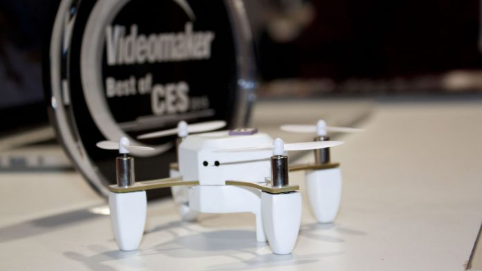 White quadcopter and award on display