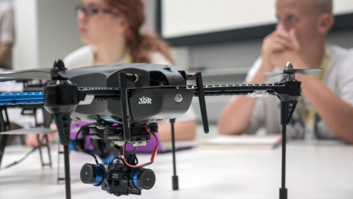 3DR's Solo drone sitting on a desk in front of students