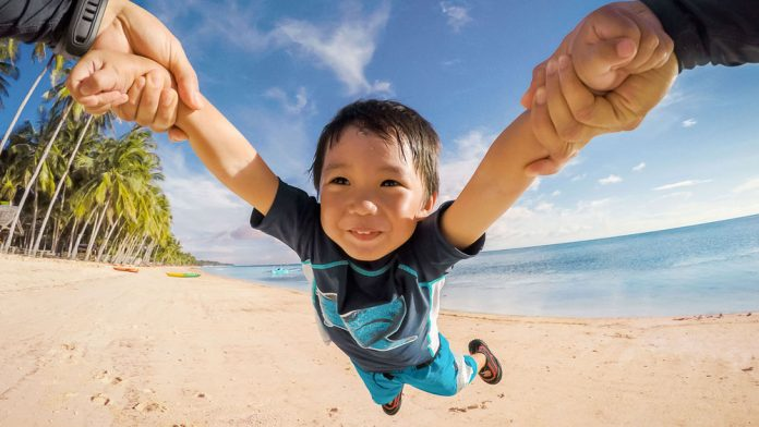 GoPro Awards promotional image of a child being lifted up on on a beach