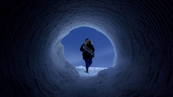 Låpsley walking into a glacier with sound equipment