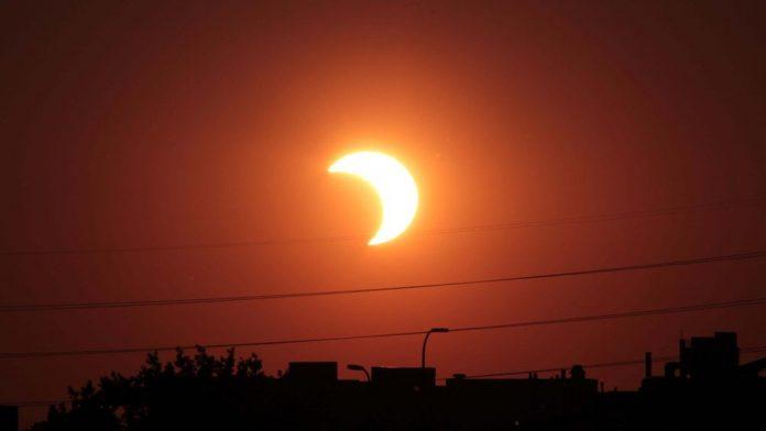 Partial solar eclipse over an industrial skyline