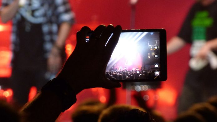 Image of someone recording a band performing on his or her phone