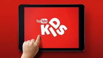 Child's hand reaching to touch tablet displaying YouTube Kids logo