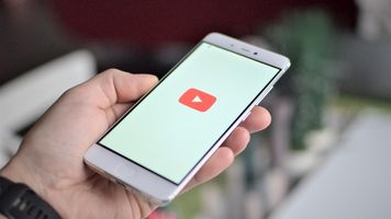 Hand holding phone with YouTube play button