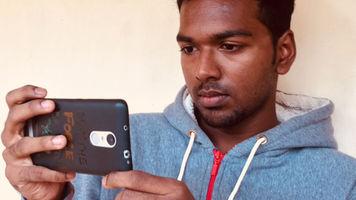 Ghanashyam Sekhar holding his smartphone