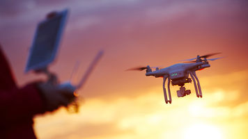 Drone flying over sunset background with its operator in the foreground