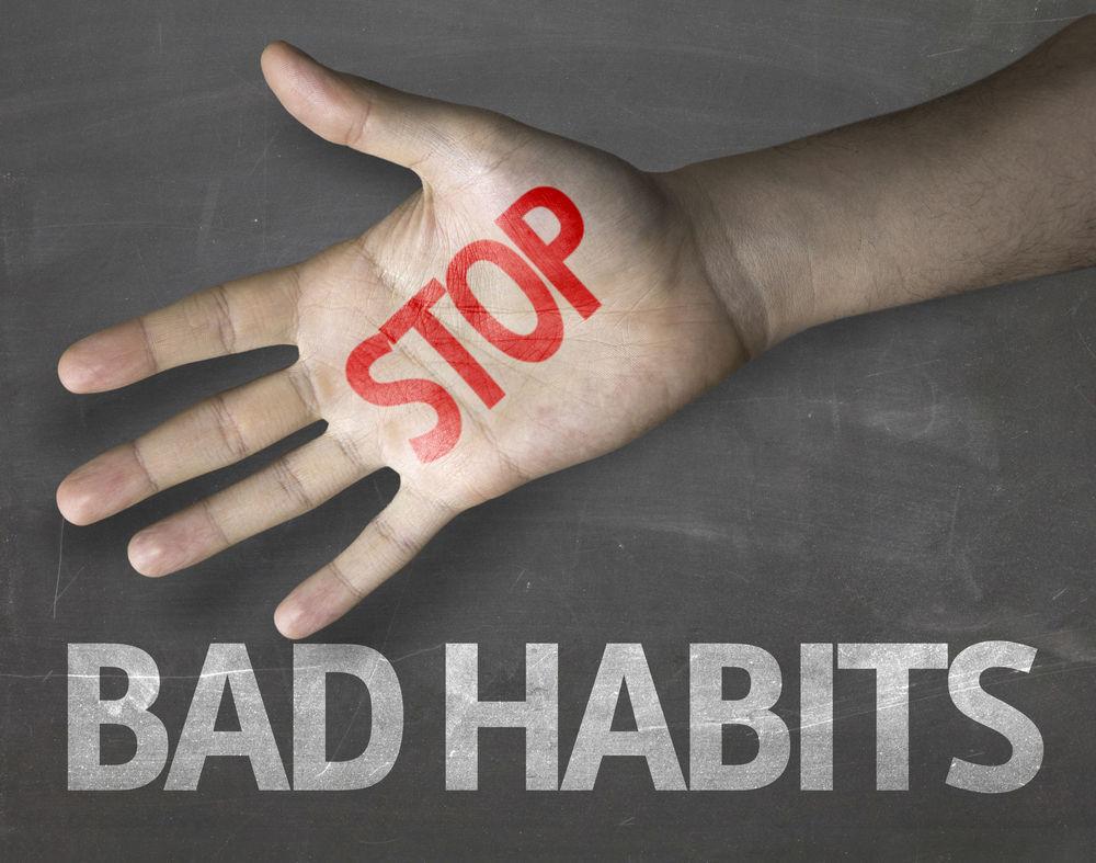 Hand with STOP written on it. Bad Habits written on chalk board.