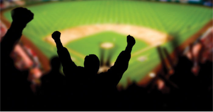 silhouette photo of fans cheering at a baseball game, the field is in sharp focus.