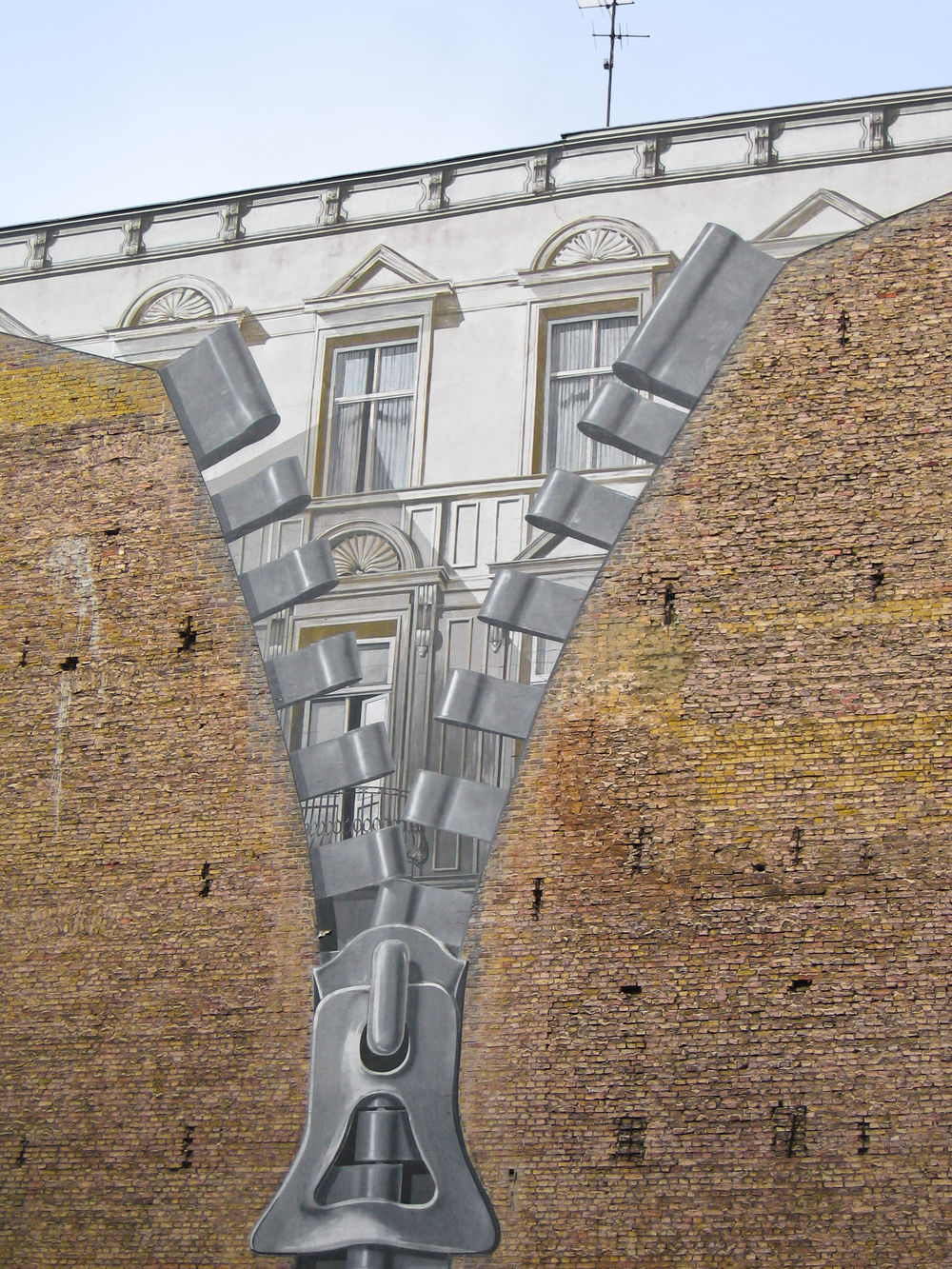 Brick wall with painting of a zipper opening up to reveal a building