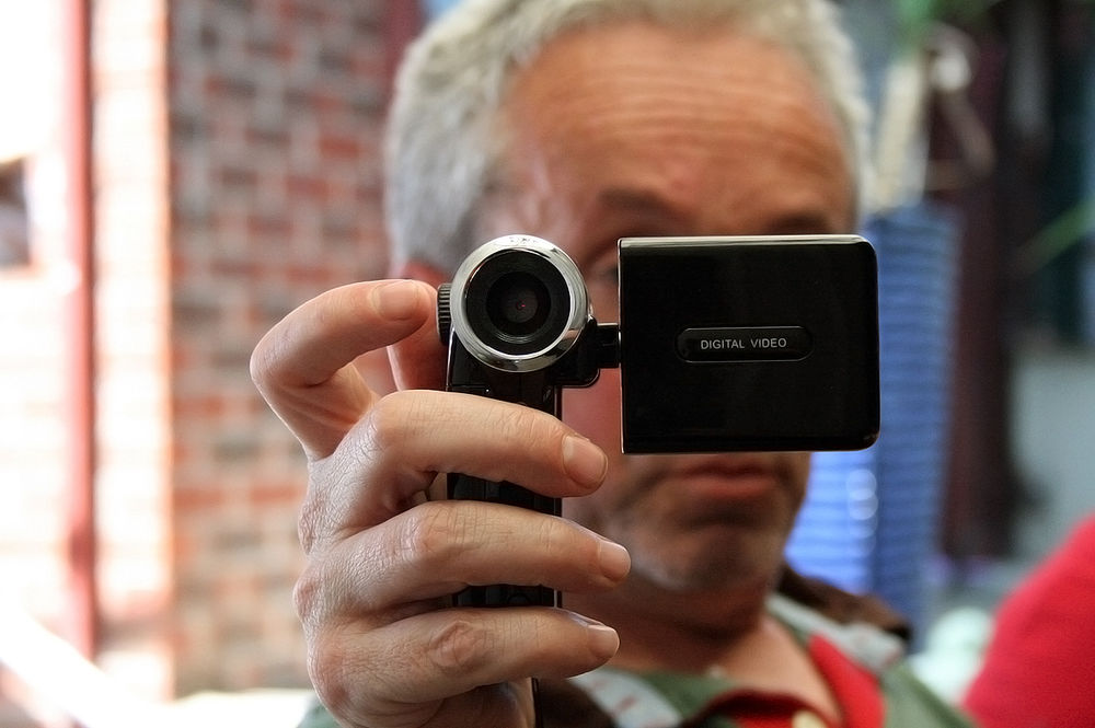 shot of a man holding a consumer camcorder