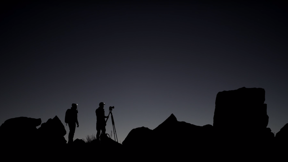 Two people and a camera on a tripod in silhouette against an open landscape