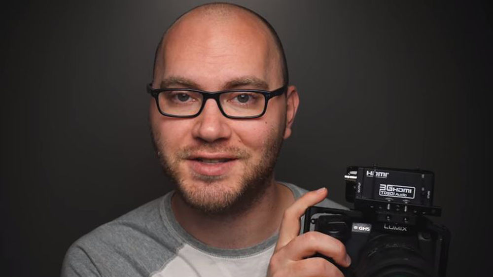 Image of Cabel Pike holding camera with his HDMI to SDI converter set up