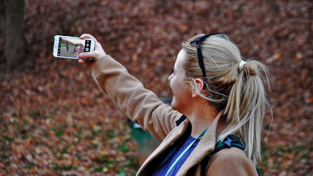 Woman holding phone up smiling