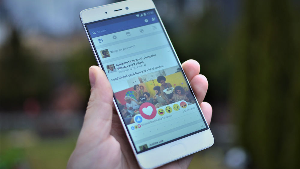 Hand holding phone displaying a Facebook post