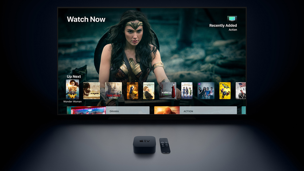 Apple TV device in front of TV displaying movies