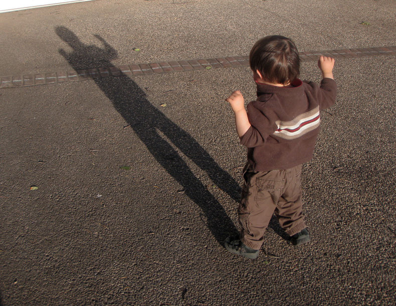 small child casting a very long shadow