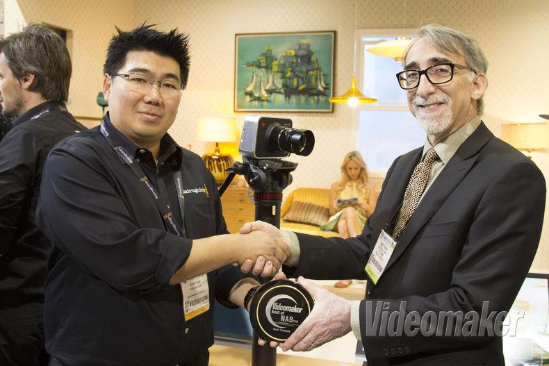 Two people shake hands and pass off an award