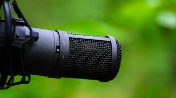 Image of microphone over green blurred background