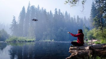 R1 flying over a lake filming a person