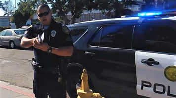 Officer James Everette pointing his gun at a videographer