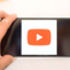 A hand holding a phone with YouTube's play icon on it