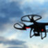 Silhouetted drone flying in a cloudy sky