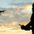 Silhouette of a person flying a drone