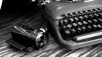 Shot of an old typewriter on a desk next to a modern camcorder
