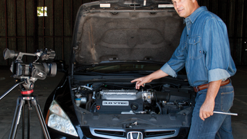 A mechanic in an auto shop is showing an audience how to work on an engine.