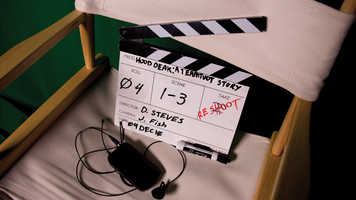 Photo of a director's chair with a slate on it. Reshoot is written in red over the Take number.