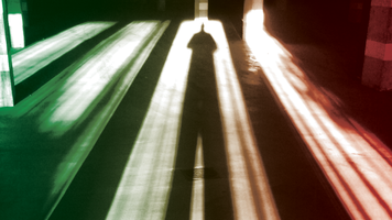Photo of the long shadow cast by a person across a floor, tinted green and red.