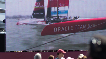 Large screen display showing the 2013 America's Cup yacht race in San Francisco