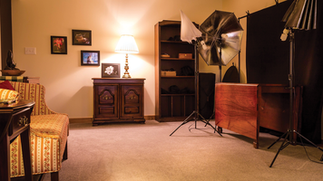 Studio set up with furniture, lamp and artwork on the walls.