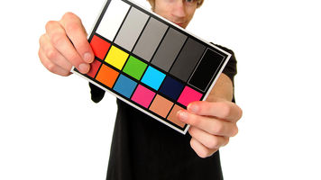 Photographer holding color and white balance chip card