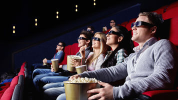people with 3D glasses on, sitting in a theater, lights down and popcorn in hand