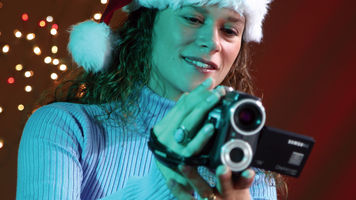 Woman in Santa Hat with a Camcorder