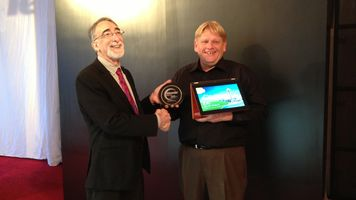 Two people at a tradeshow hold a plaque and a tablet