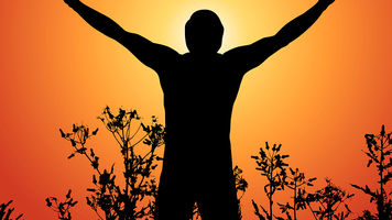silhouette of a man in a field against an orange sky