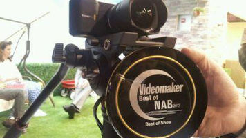 Blackmagic Pocket Cinema Camera on a tripod with an award held in front