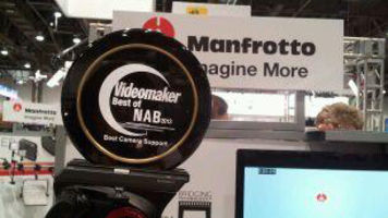 Manfrotto tripod with award on top with signs and monitor behind