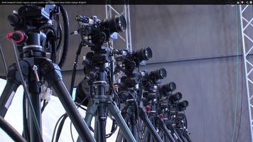 numerous cameras lined up on tripods aiming at one point