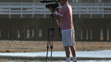 A videographer shooting video using a tripod